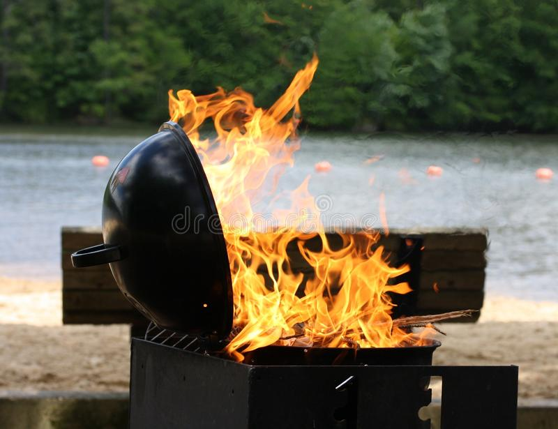 Barbecue Grill. Flames shoot from lakeside barbecue grill royalty free stock images