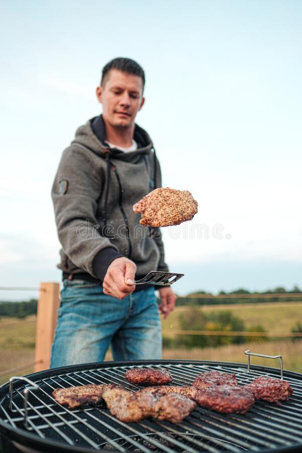 Barbecue grill. A man fries meat steaks and meatballs for hamburgers, turns the meat over with tongs. The concept of cooking meat outdoor royalty free stock photography