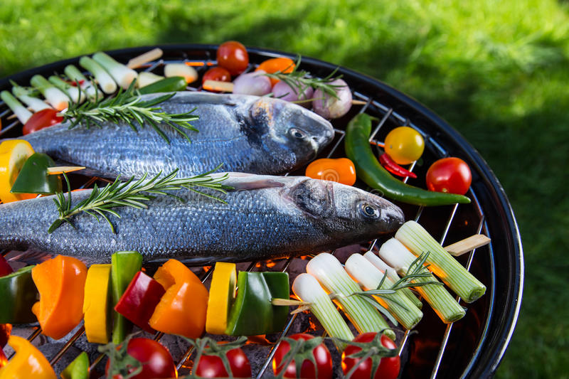 Barbecue grill with sea fishes. Barbecue grill with sea fishes on green grass, close-up stock photo