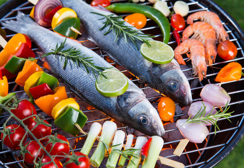 Barbecue grill with sea fishes. Barbecue grill with sea fishes on green grass, close-up royalty free stock photos