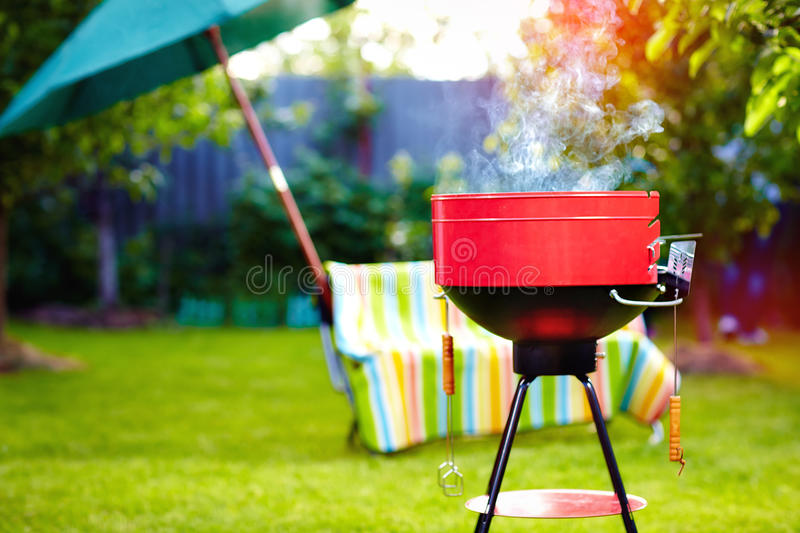 Barbecue grill with smoke on summer backyard party stock photos