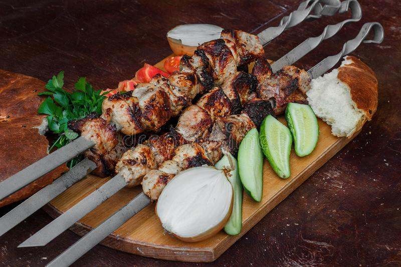 Grilled meat skewers, shish kebab, healthy vegetable fresh tomato, cucumber, onion and bread royalty free stock images