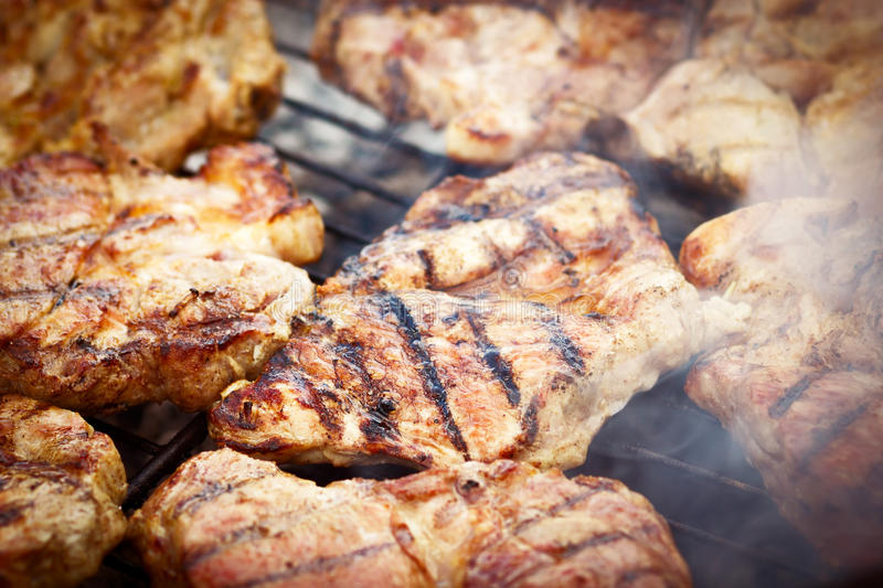 Barbecue. Meat on barbecue grill flames stock photos