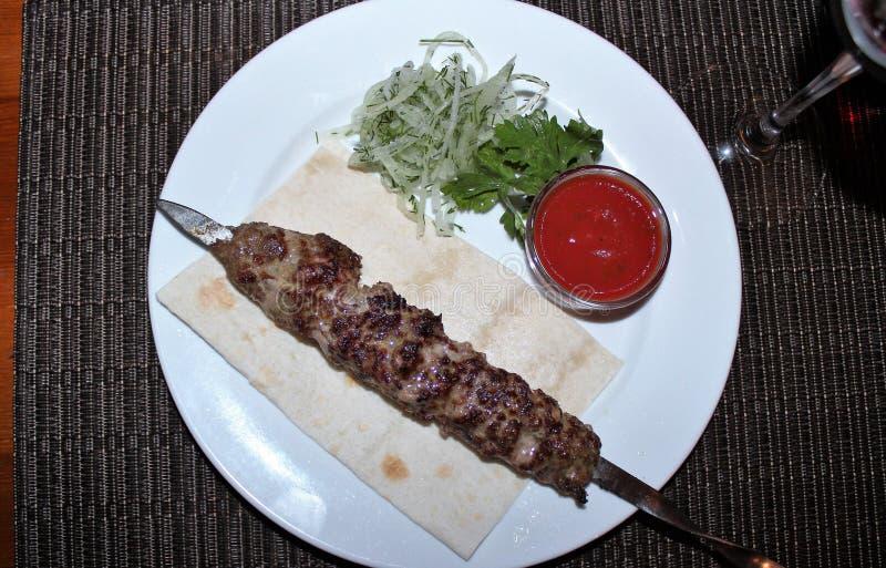 Barbecue met tomatensaus en salade op een witte plaat De mening vanaf de bovenkant royalty-vrije stock fotografie