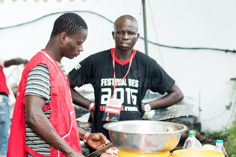 Barbecue party in Abidjan. Abidjan, Ivory Coast, September 11 2016: barbecue party at abidjan.Two young men standing in a red waistcoat cut chicken meat and the stock photo
