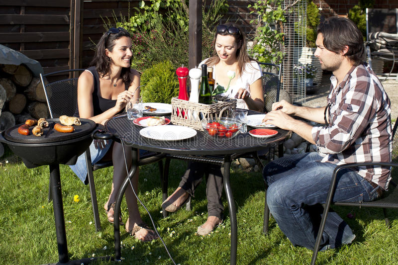 Barbecue party in the garden. Three people enjoying a barbecue party in the garden stock image