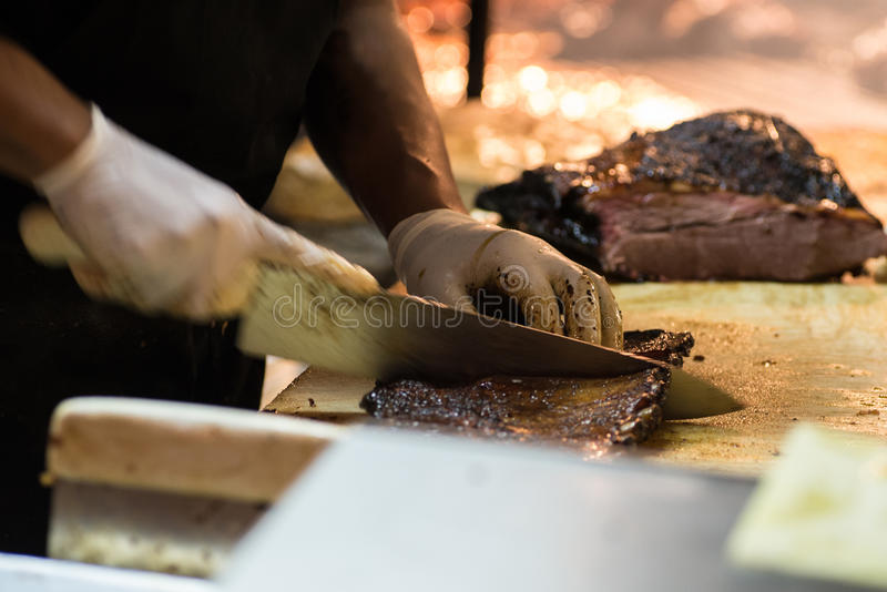 Barbecue pitmaster cutting through a slab or pork ribs with a br stock photo