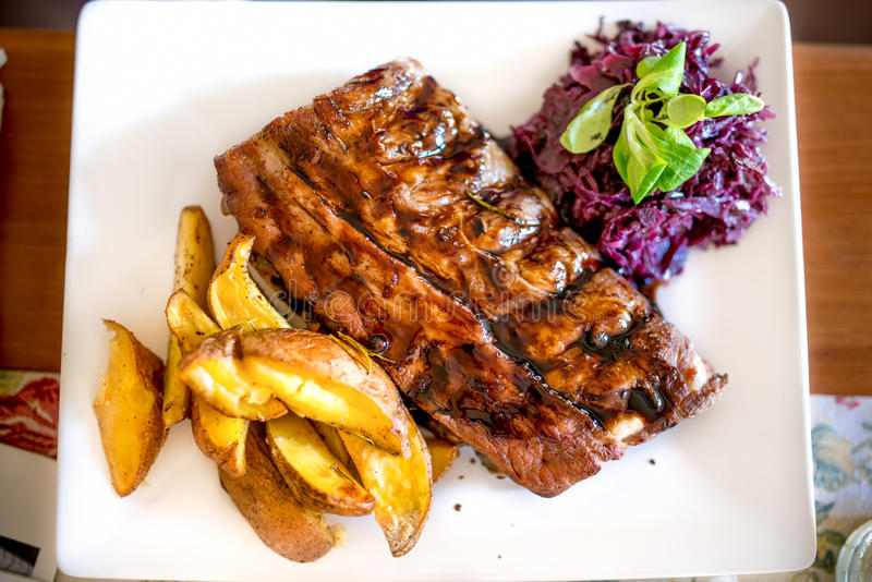 Barbecue pork ribs as main dish at restaurant. Pork delicacy with delicious barbecue sauce, cabbage and potatoes stock photography