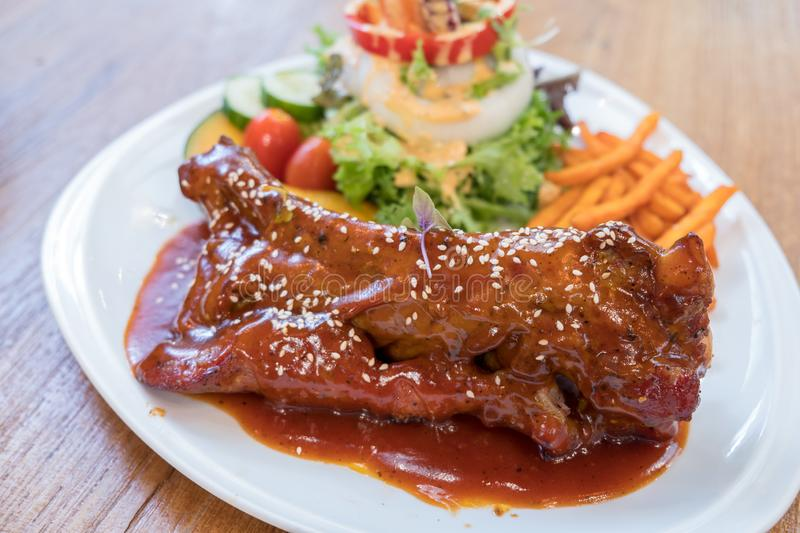 Barbecue pork ribs with fried sweet potatoes and mixed salad on white plate. royalty free stock images
