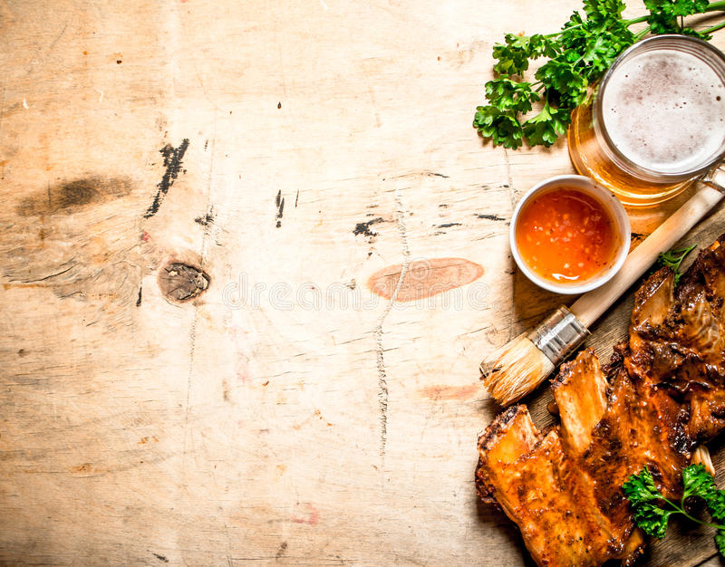 Barbecue pork ribs with tomato sauce and beer. On wooden background royalty free stock photos