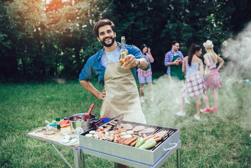 Barbecue preparante maschio all'aperto per gli amici fotografia stock libera da diritti