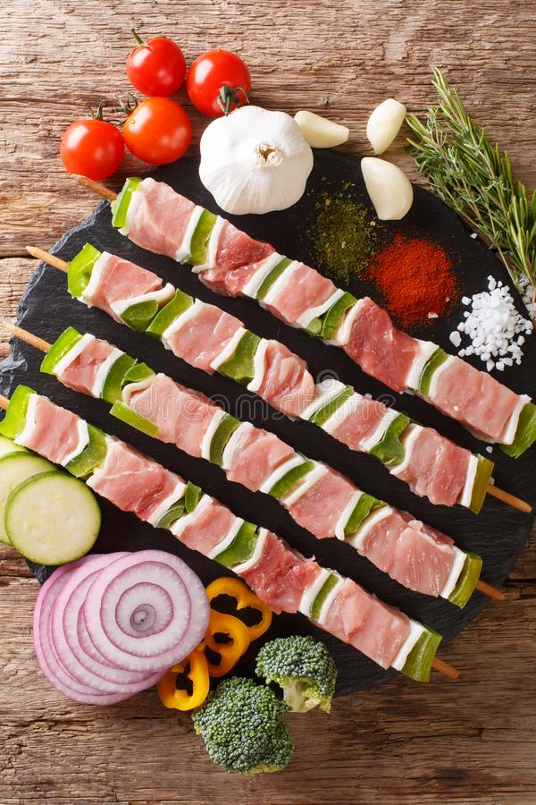 For barbecue raw shish kebab with pepper and lard on skewers close-up and ingredients, vegetables, spices, herbs. Vertical top vi royalty free stock photo