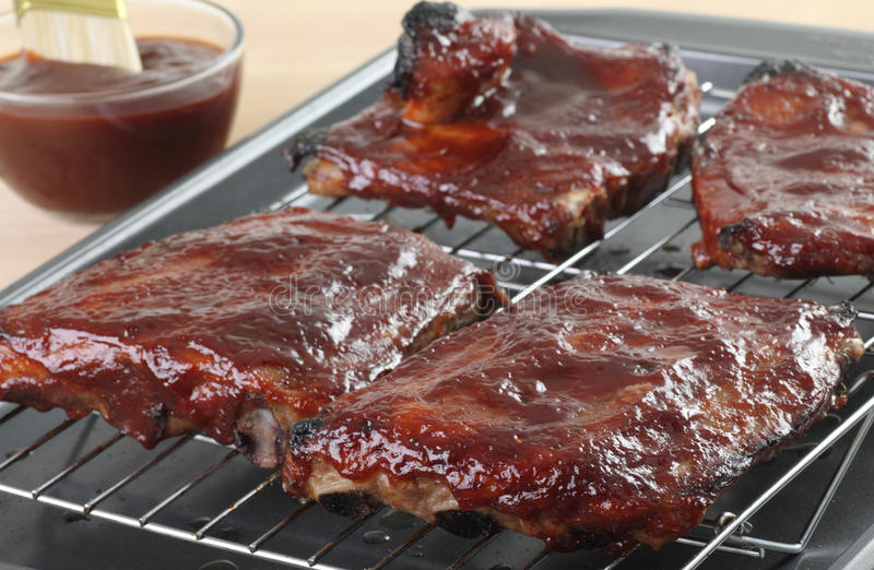 Barbecue Ribs. Barbecue spareribs on a broiling oven rack stock photo