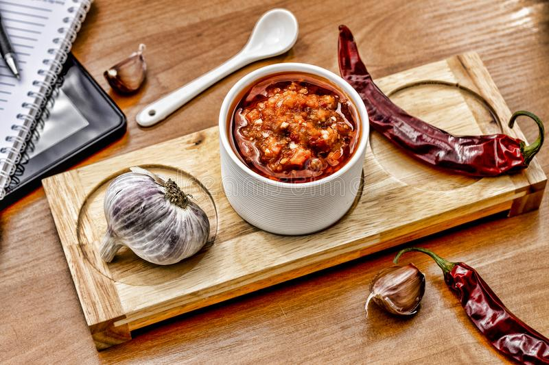 Barbecue sauce in a ceramic bowl and spoon on the wooden table in a cafe or restaurant. The concept: business lunch. royalty free stock photos