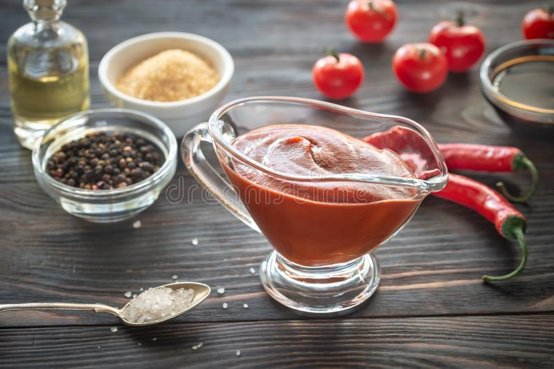 Barbecue sauce in gravy boat. Barbecue sauce in glass gravy boat with the ingredients royalty free stock photos