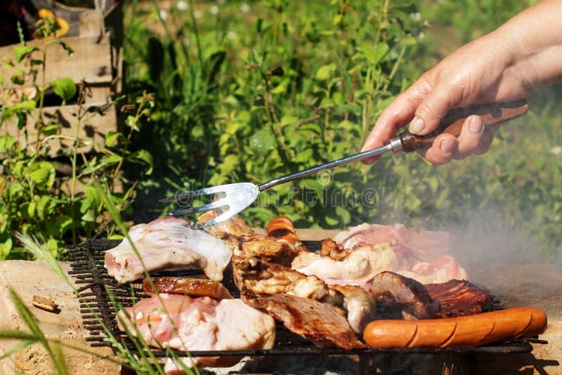 Barbecue Saucisses, cuisses de poulet, biftecks, lard sur une grille de gril photo libre de droits