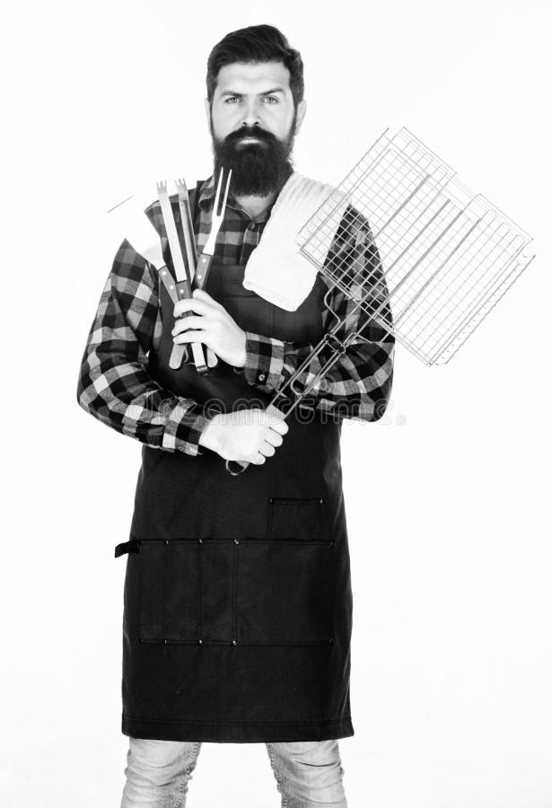 Barbecue season. Bearded hipster wear apron for barbecue. Roasting and grilling food. Man hold cooking utensils barbecue royalty free stock image