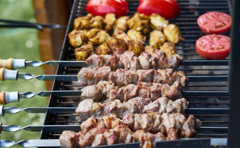 Barbecue shashlik kebab with winglets and tomatoes with roasted pepper in chargrill semifinished on skewer side view closeup. Marinated barbecue shashlik kebab stock photos