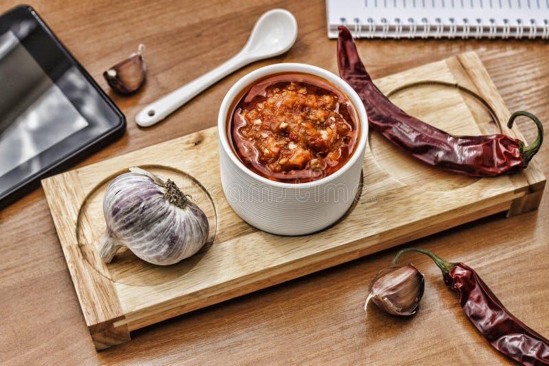Barbecue-Soße in einer keramischen Schüssel und in einem Löffel auf dem Holztisch in einem Café oder in einem Restaurant Das Konz stockbild