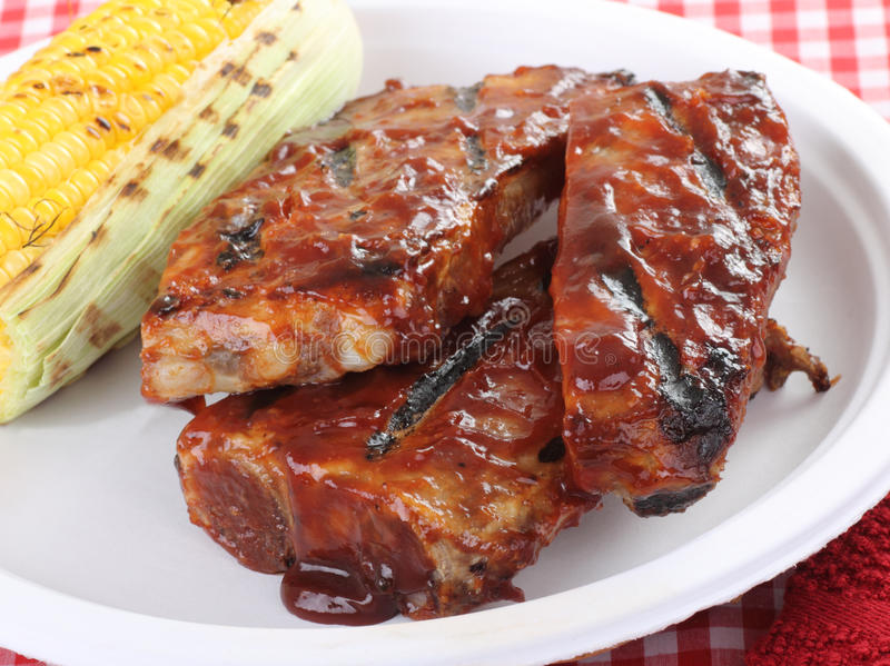 Barbecue Spareribs. Grilled barbecue spareribs and ear of corn on a plate royalty free stock photos
