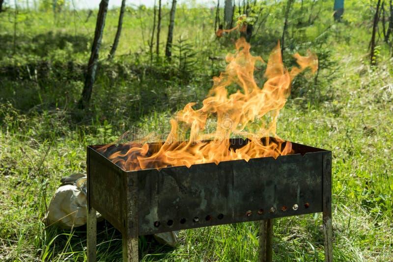 Barbecue sulla griglia di estate all'aperto, accensione dei carboni fotografia stock