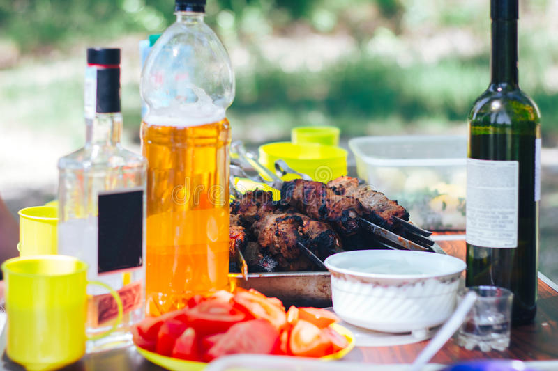 Barbecue on table with wine beer nature. Barbecue in the backyard on table with wine beer stock image