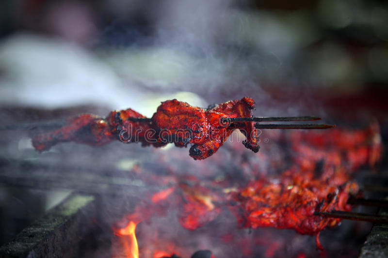 Barbecue Tandoori Chicken. Delicious tandoori chicken on a barbecue covered with Indian delicious spices stock images