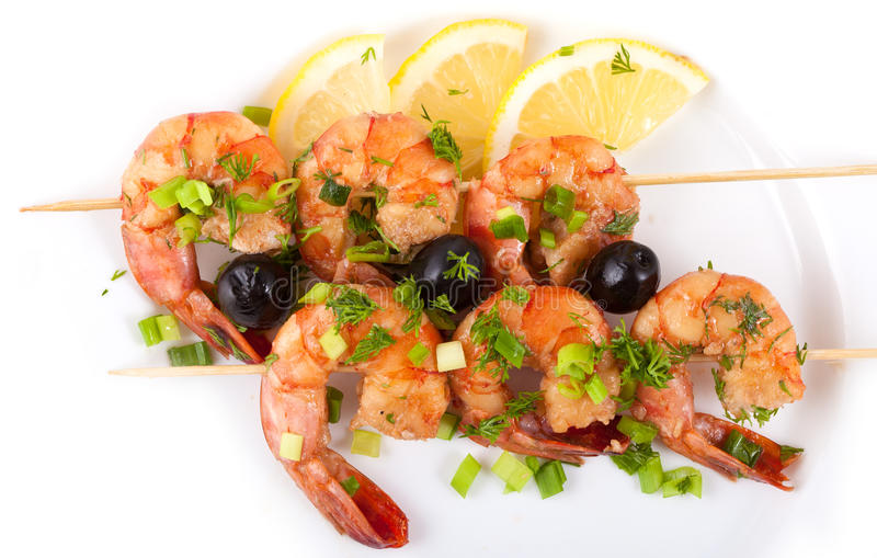 Barbecue with Tiger Prawns. On a Skewer with Olives and Lemon on white Background royalty free stock images