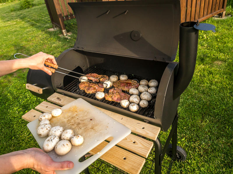 Barbecue time. Red meat chops and champignons being placed on barbecue stock images