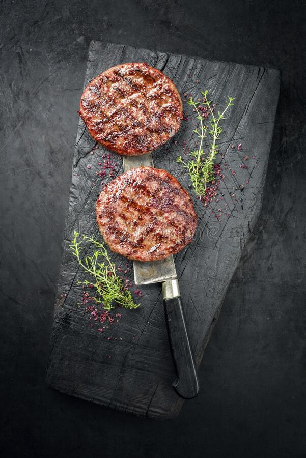 Free Barbecue Wagyu Hamburger With Red Wine Salt And Herbs On A Charred Wooden Board Stock Images - 194399864