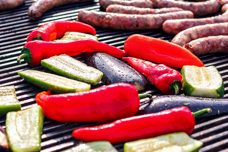 Barbecue with zucchini, red pepper, eggplant and juicy sausages grilled over charcoal. Vegetables and meat on the grill over low royalty free stock photos
