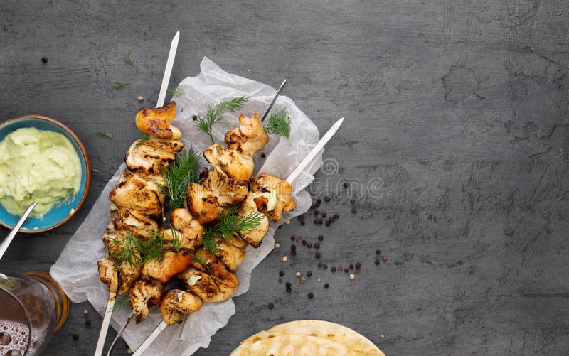 barbecued chicken breast skewers with flat bread and avocado sauce royalty free stock photo