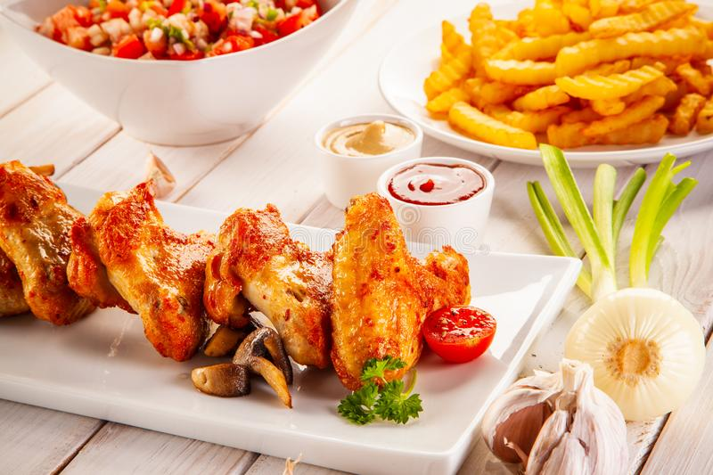 Barbecued chicken wings with french fries and vegetable salad on timber royalty free stock images