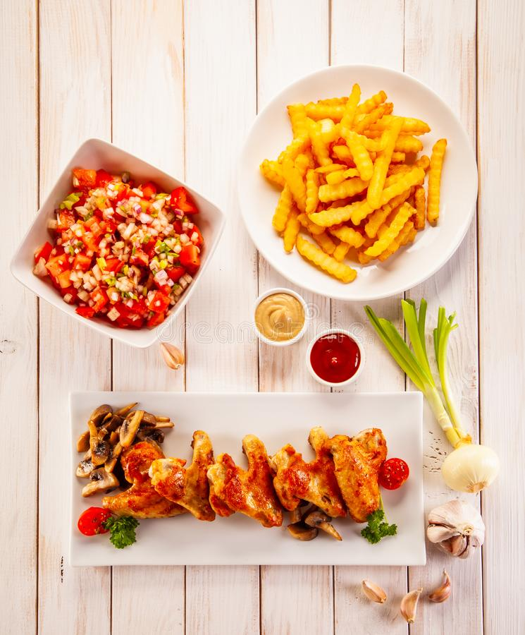Barbecued chicken wings with french fries and vegetable salad on timber stock photos