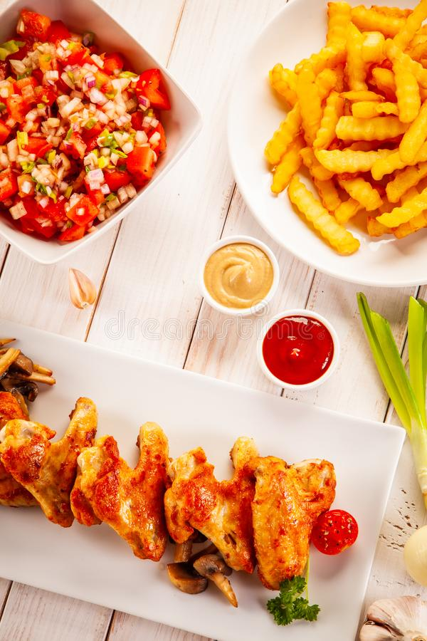 Barbecued chicken wings with french fries and vegetable salad on timber stock images