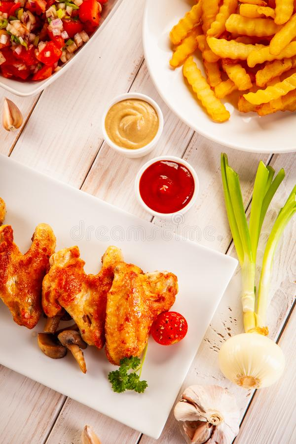 Barbecued chicken wings with french fries and vegetable salad on timber stock photo