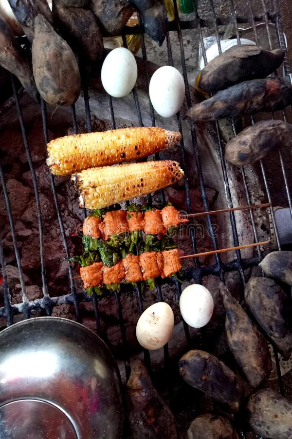 Barbecued food - eggs, mutton, sweet potatoes and corns stock photo