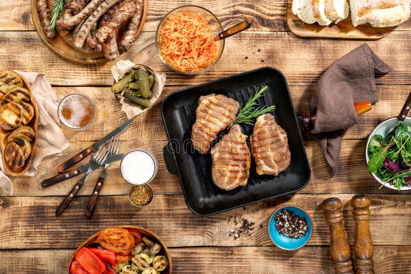 Barbecued steak, sausages, beer and grilled vegetables on wooden royalty free stock photography
