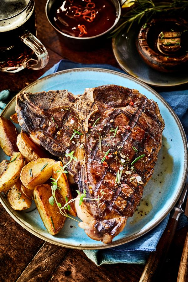 Barbecued T-bone steak with fresh herbs royalty free stock images