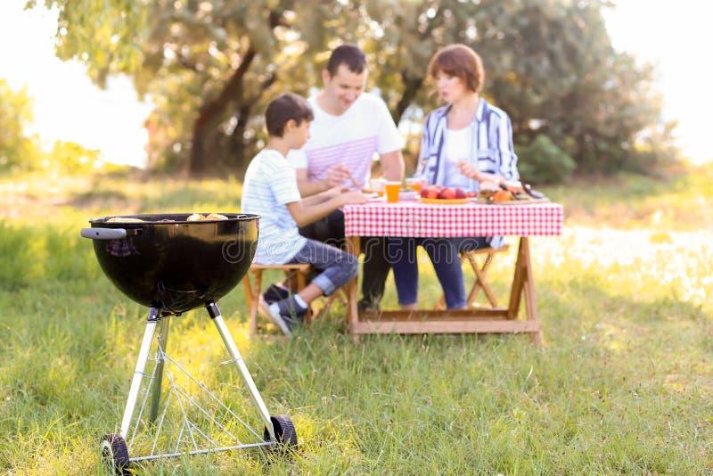 Barbecuegrill met smakelijk voedsel dichtbij familie die picknick in park hebben royalty-vrije stock foto