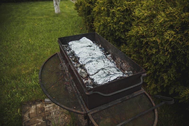 Barbecuegrill waarin de vis in folie wordt gebakken royalty-vrije stock foto's