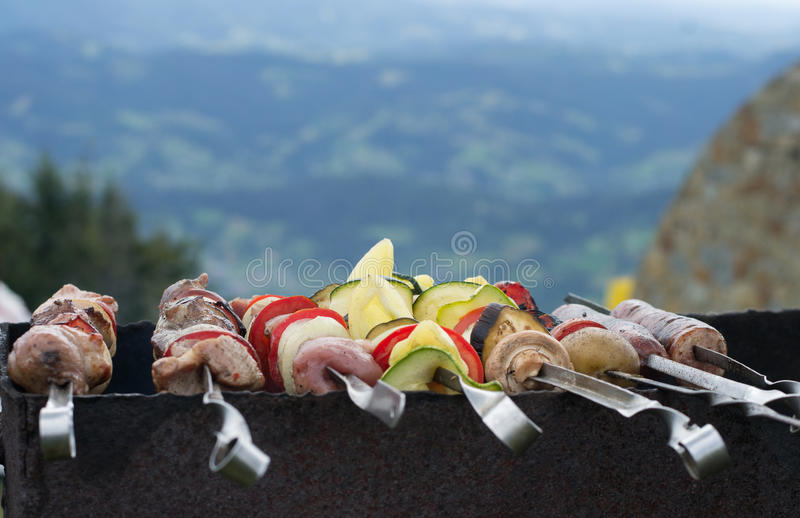 Barbecueing meat, vegetables and mushrooms outdoors stock photo