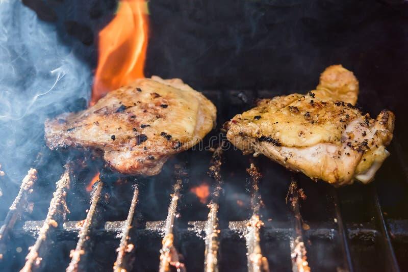 Barbecuekip op een grill met vlammen die van de rug schieten stock afbeelding