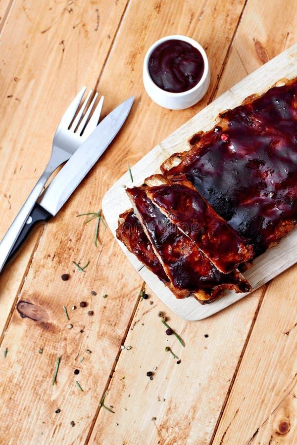 Barbecueribben op houten lijst met saus royalty-vrije stock afbeelding
