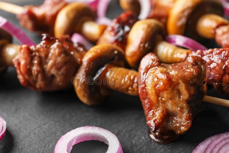 Barbecuevleespennen met sappig vlees en paddestoelen op leiplaat, close-up stock afbeelding