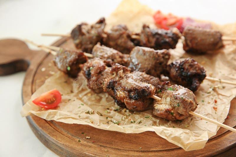 Barbecuevleespennen met sappig vlees op houten raad, close-up stock fotografie
