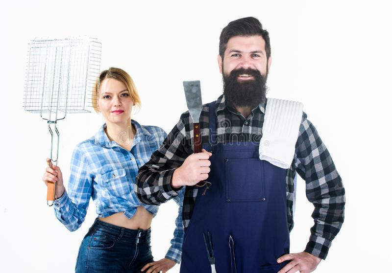 Barbecuing common technique. Essential barbecue dishes. Bearded hipster and girl hold cooking grilling utensils white royalty free stock image