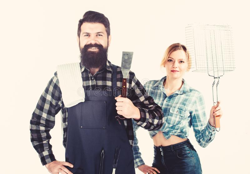 Barbecuing common technique. Essential barbecue dishes. Bearded hipster and girl hold cooking grilling utensils white royalty free stock images