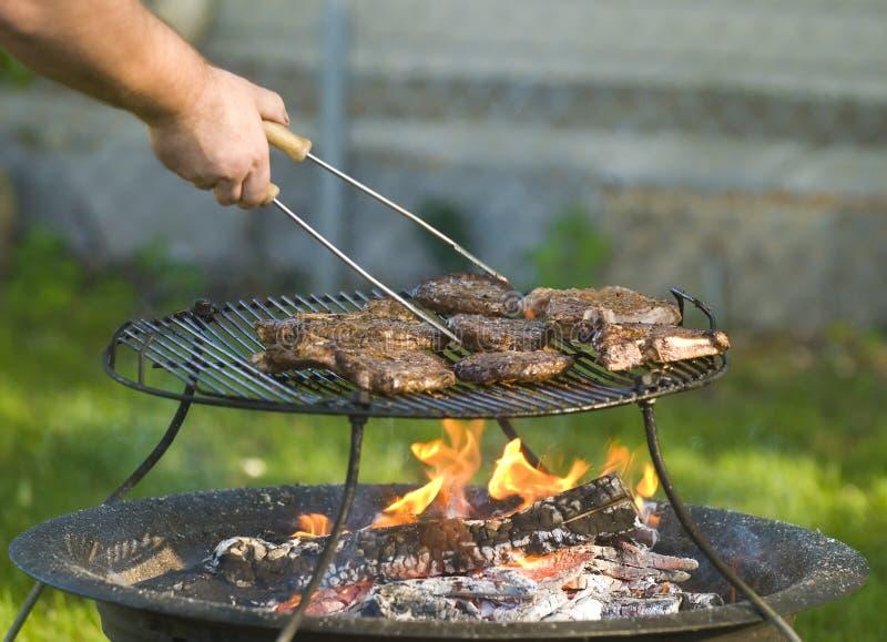 barbecuing manmeat royaltyfria bilder