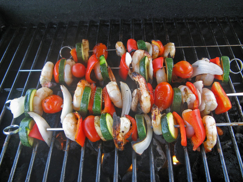 Barbecuing Shrimps & vegetables stock image